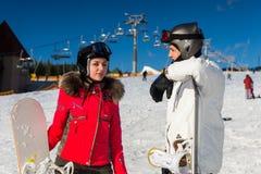 Hombre joven y mujer en trajes de esquí, cascos y standi de las gafas del esquí Foto de archivo libre de regalías