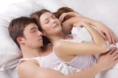 Hombre joven y mujer en una cama Imagen de archivo