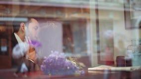 Hombre joven y mujer europea morena atractiva en el vestido blanco que se besan apasionado en el café por la ventana en a metrajes