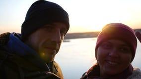 Hombre joven y mujer fotografiados por el río en el fondo de la puesta del sol en el otoño, demostración de los pares en la cámar almacen de video