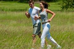 Hombre joven y mujer que activan en un prado Fotografía de archivo