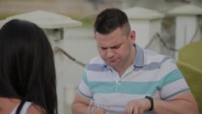 Hombre joven y mujer que almuerzan en un restaurante en la terraza al aire libre almacen de video