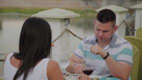 Hombre joven y mujer que almuerzan en un restaurante en la terraza al aire libre metrajes