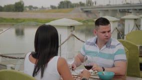 Hombre joven y mujer que almuerzan en un restaurante en la terraza al aire libre almacen de metraje de vídeo
