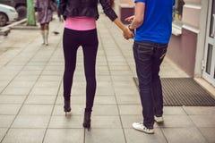 Hombre joven y mujer que caminan abajo de la calle Imagen de archivo libre de regalías
