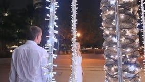 Hombre joven y mujer que caminan entre árboles de palmas que brillan intensamente en la noche en la ciudad Muchacha con el amor q metrajes