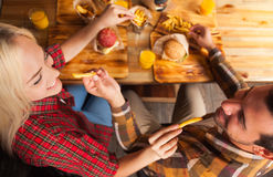 Hombre joven y mujer que comen la patata de los alimentos de preparación rápida que se sienta en la tabla de madera en la opinión Foto de archivo