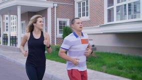 Hombre joven y mujer que corren con la determinación en la calle de la ciudad metrajes