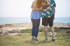 Hombre joven y mujer que disfrutan de la visión en la costa Imágenes de archivo libres de regalías