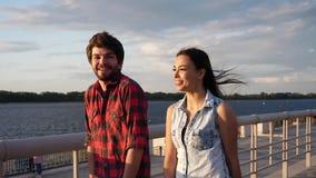 Hombre joven y mujer que disfrutan del día soleado que toma un paseo al lado del río, de hablar y de la risa metrajes