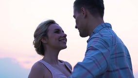 Hombre joven y mujer que disfrutan del tiempo junto que besa la puesta del sol, luna de miel, conexión almacen de metraje de vídeo