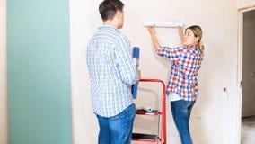 Hombre joven y mujer que eligen los papeles pintados en su nuevo apartamento Fotografía de archivo