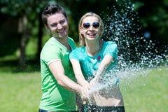 Hombre joven y mujer que juegan con el aerosol de agua Foto de archivo libre de regalías