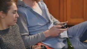 Hombre joven y mujer que juegan en las palancas de mando almacen de video