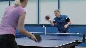 Hombre joven y mujer que juegan a tenis de mesa almacen de video
