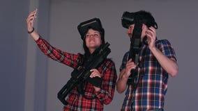 Hombre joven y mujer que llevan los vidrios y los armas de la realidad virtual que toman selfies en el teléfono almacen de metraje de vídeo