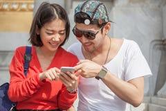 Hombre joven y mujer que miran al uso elegante de la pantalla del teléfono para moderno Imagen de archivo libre de regalías
