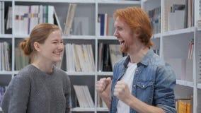 Hombre joven y mujer que reaccionan al éxito, opinión de la cámara metrajes