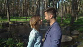 Hombre joven y mujer que se besan al aire libre almacen de metraje de vídeo