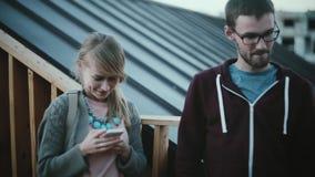 Hombre joven y mujer que se colocan en el balcón, caminando en centro de ciudad Hembra hermosa que usa el smartphone, varón cerca almacen de metraje de vídeo