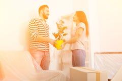 Hombre joven y mujer que se colocan en sala de estar después de volver a poner Imágenes de archivo libres de regalías