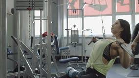 Hombre joven y mujer que se relajan y que ejercitan en el gimnasio almacen de metraje de vídeo