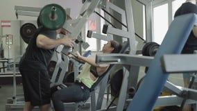 Hombre joven y mujer que se relajan y que ejercitan en el gimnasio almacen de video