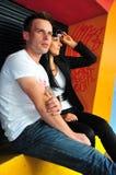 Hombre joven y mujer que se sientan al aire libre Fotografía de archivo libre de regalías