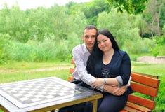 Hombre joven y mujer que se sientan en un banco de parque. Fotografía de archivo