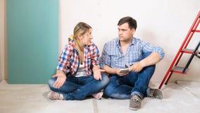 Hombre joven y mujer que tienen conflicto en nueva casa bajo construcción imágenes de archivo libres de regalías