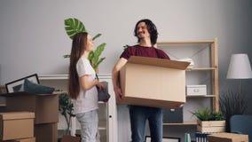 Hombre joven y mujer que traen cosas en cajas al nuevo apartamento y a besarse almacen de metraje de vídeo