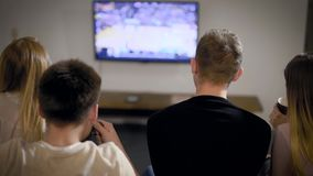 Hombre joven y mujer que ven la TV almacen de metraje de vídeo
