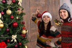 Hombre joven y mujer sonrientes que adornan el árbol de navidad en su l Foto de archivo