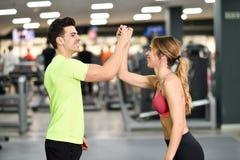 Hombre joven y mujer sonrientes que hacen el alto cinco en gimnasio Imagenes de archivo