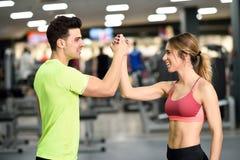 Hombre joven y mujer sonrientes que hacen el alto cinco en gimnasio Foto de archivo libre de regalías