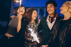 Hombre joven y mujeres en ciudad en la noche con los fuegos artificiales fotos de archivo libres de regalías