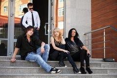 Hombre joven y mujeres que se sientan en los pasos Fotografía de archivo