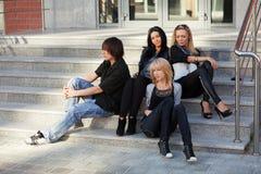 Hombre joven y mujeres que se sientan en los pasos Fotografía de archivo libre de regalías
