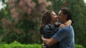 Hombre joven y reunión atractiva de la mujer en la calle durante un tiempo lluvioso La muchacha con el pelo rizado la está abraza almacen de video