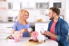 Hombre joven y su mamá madura que desayunan en cocina fotografía de archivo