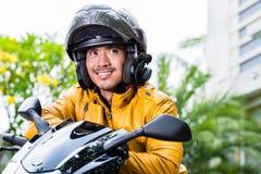 Hombre joven y su motocicleta o vespa Imagenes de archivo