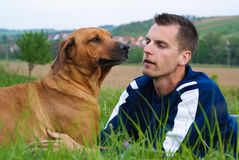 Hombre joven y su perro Imagenes de archivo