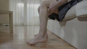 Hombre jubilado con el calambre muscular que se sienta en el dormitorio que frota su pierna que cura la tensión desagradable - metrajes