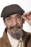 Hombre jubilado con los vidrios y el sombrero del vendedor de periódicos Imagen de archivo