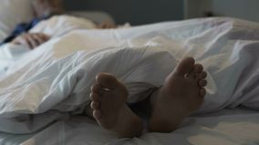 Hombre jubilado que duerme en la cama, el olor desagradable y el malestar debido al hongo de pie Imágenes de archivo libres de regalías