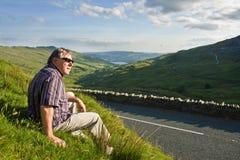 Hombre jubilado que se reclina cerca del camino Imagenes de archivo