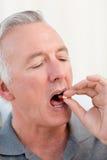 Hombre jubilado que toma píldoras Fotografía de archivo