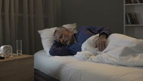 Hombre jubilado que ve pesadillas en sus sueños, durmiendo en la sala de la clínica de reposo fotos de archivo libres de regalías