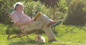 Hombre jubilado y perro mayores que se relajan al aire libre leyendo un libro que disfruta del retiro almacen de video