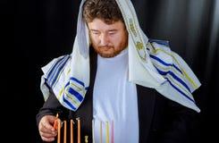 Hombre judío con la barba que enciende las velas para el hannukah fotografía de archivo